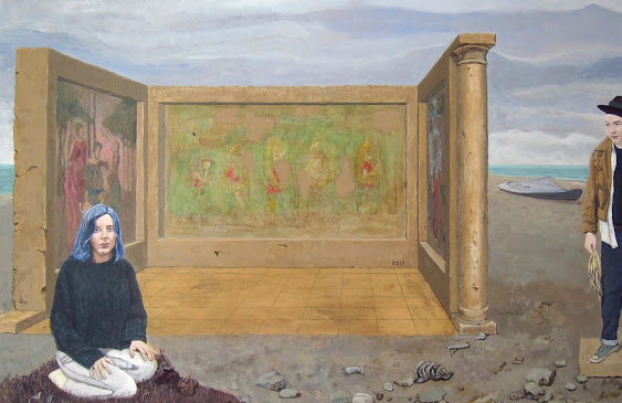 A woman kneeling on the beach and a man standing next to her.
