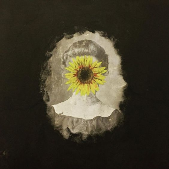 A portrait of a woman with a flower blocking her face.